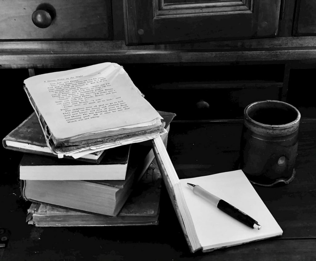 black and white photo of books on a desk